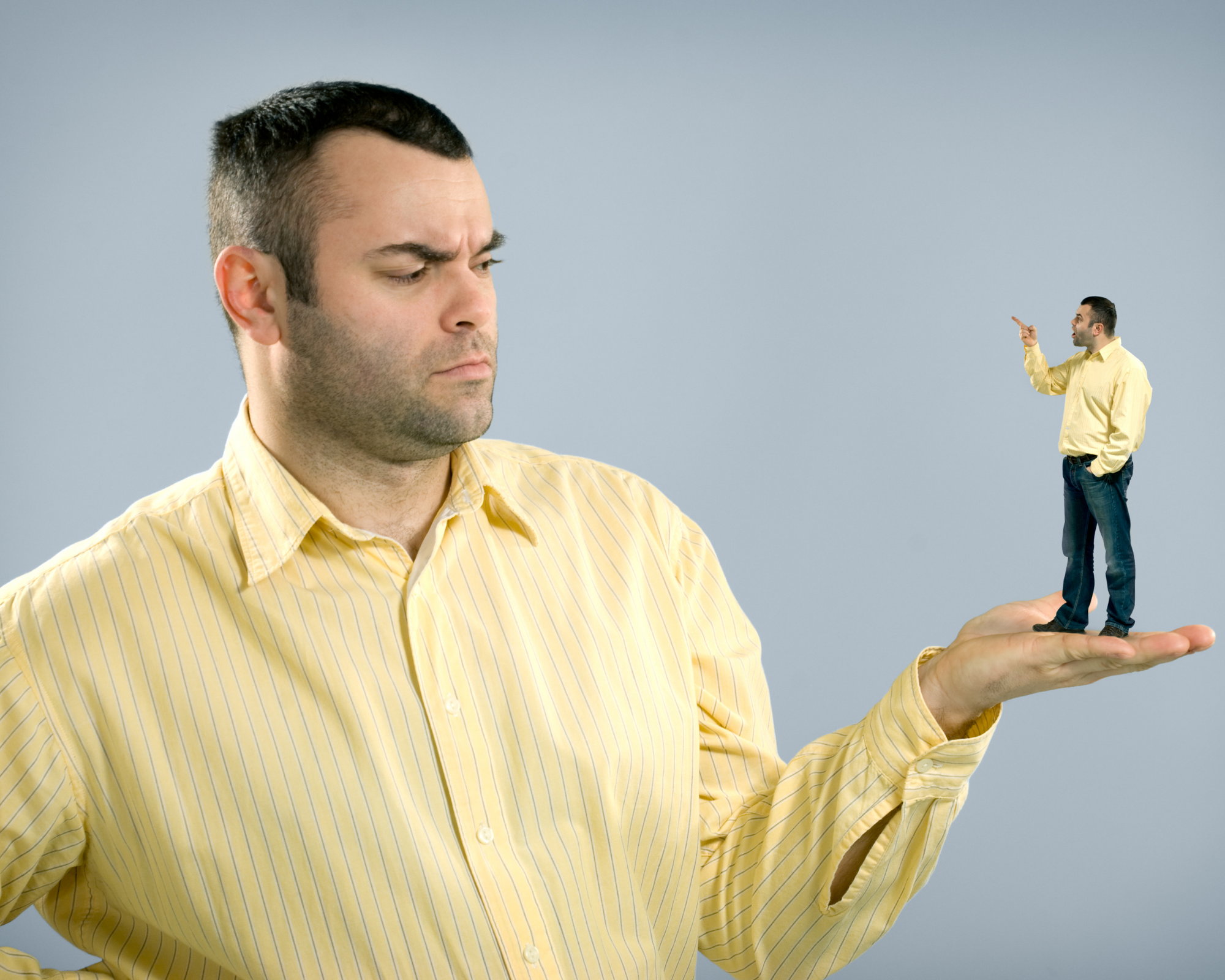 Man with negative self-talk. Man frowning with small version of himself on his palm and pointing accusingly